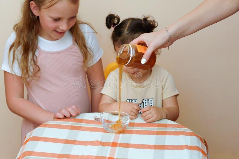看在妇女手上的两滑稽的逗人喜爱的女孩接近的画象倒从瓶子的新鲜的蜂蜜入碗 免版税库存照片