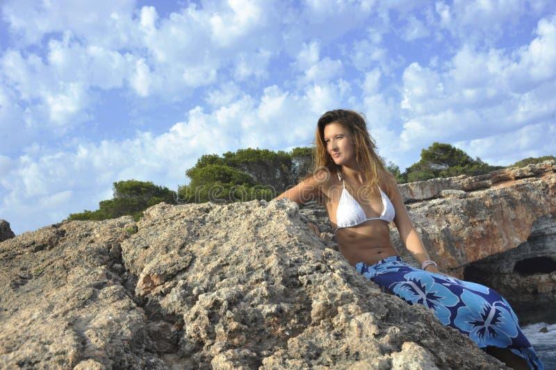 看在岩石峭壁的妇女海洋天际由在布裙海滩套的海岸 库存图片