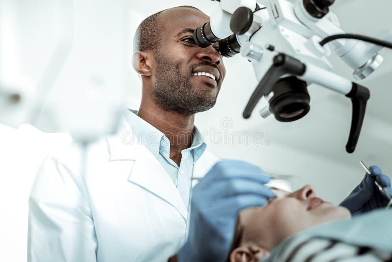 看在巨型显微镜的英俊的正面牙医 库存图片