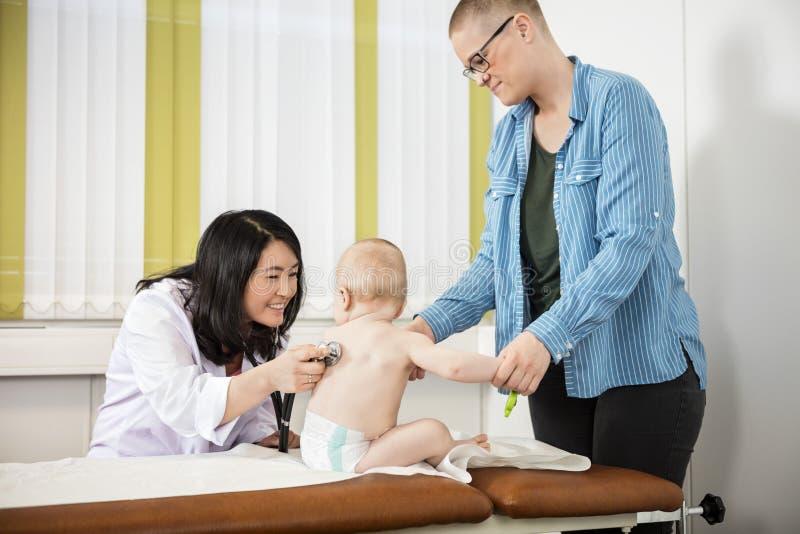 看在床上的母亲微笑的儿科医生审查的婴孩 免版税库存图片