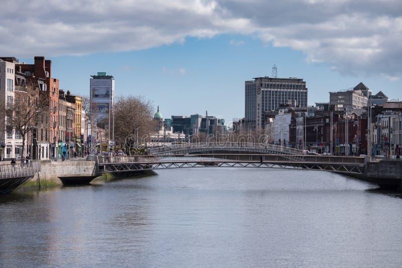 看在往Ha `便士桥梁和千年桥梁的利菲河下的都伯林市 免版税库存照片