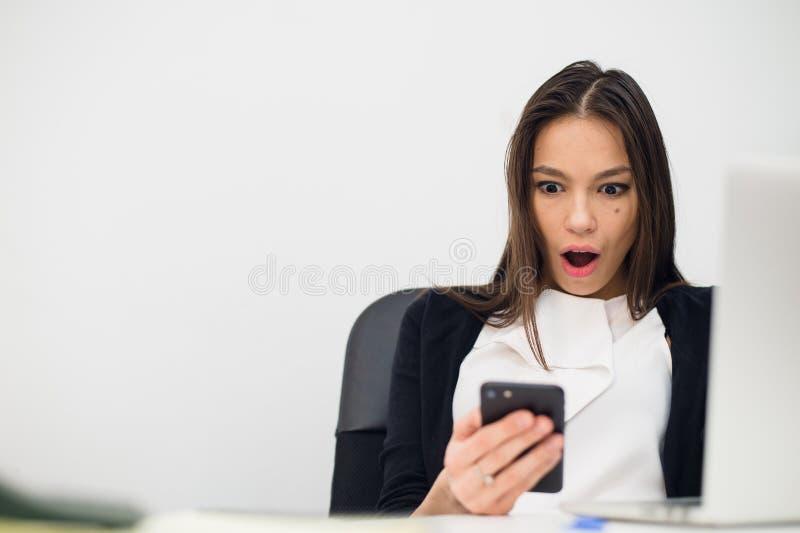 看在手机和读与开放嘴的愉快的惊奇的妇女消息 库存图片
