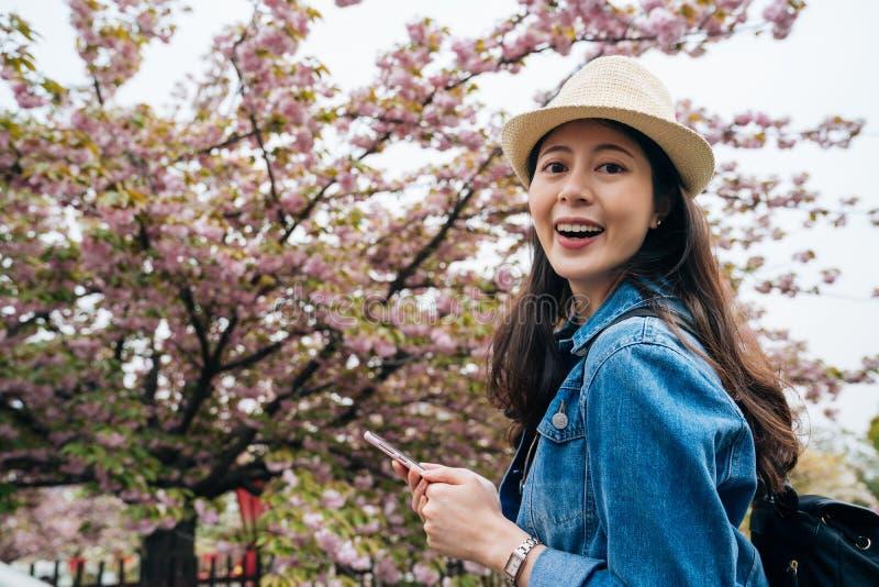 看在手机的快乐的旅客网上指南应用程序参观在日本薄菏的美丽的樱桃树 害怕表面女孩纵向惊奇的年轻人 图库摄影