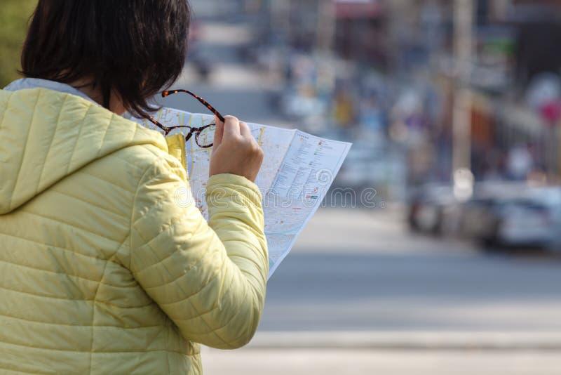 看在打印的纸地图的外国女性模型寻找f 免版税库存图片