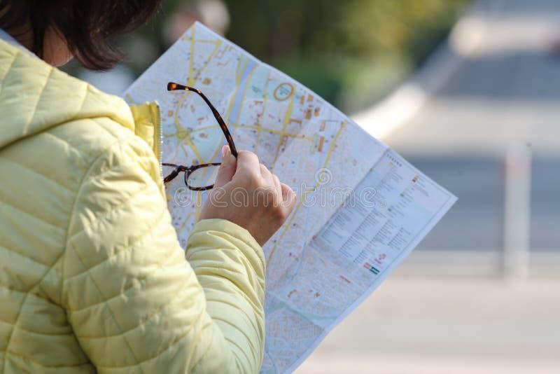看在打印的纸地图的外国女性模型寻找f 免版税库存照片