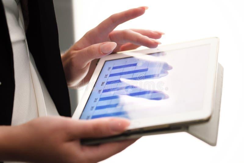 看在数字式片剂的年轻女实业家特写镜头图表 免版税库存照片