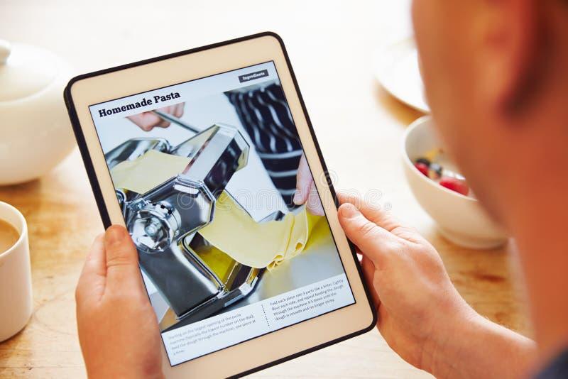 看在数字式片剂的早餐的人食谱App 免版税库存图片