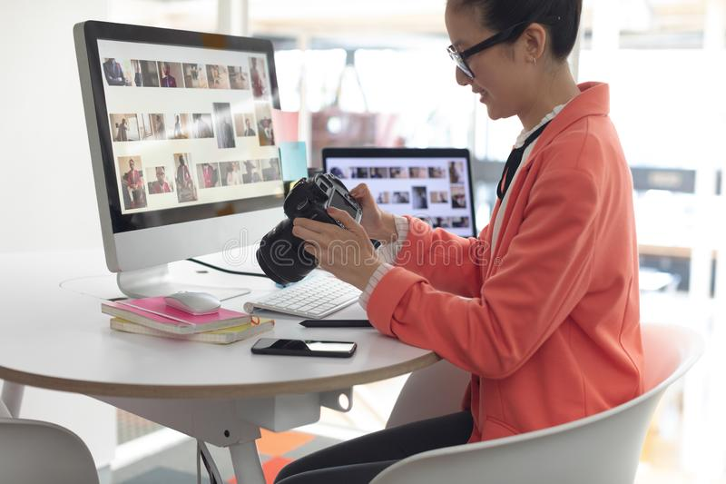 看在数码相机的女性图表设计师照片书桌在一个现代办公室 库存照片