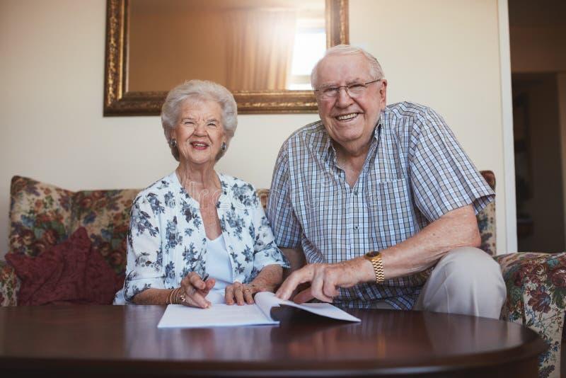 看在文件的微笑的退休的夫妇 库存图片
