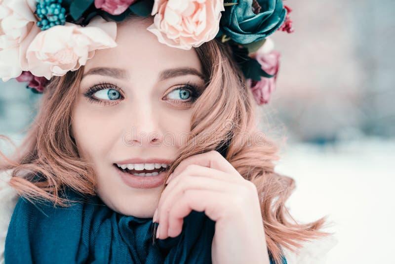 看在旁边佩带花卉头饰带冠状头饰冠和围巾被隔绝的冬天背景的年轻女人 库存图片
