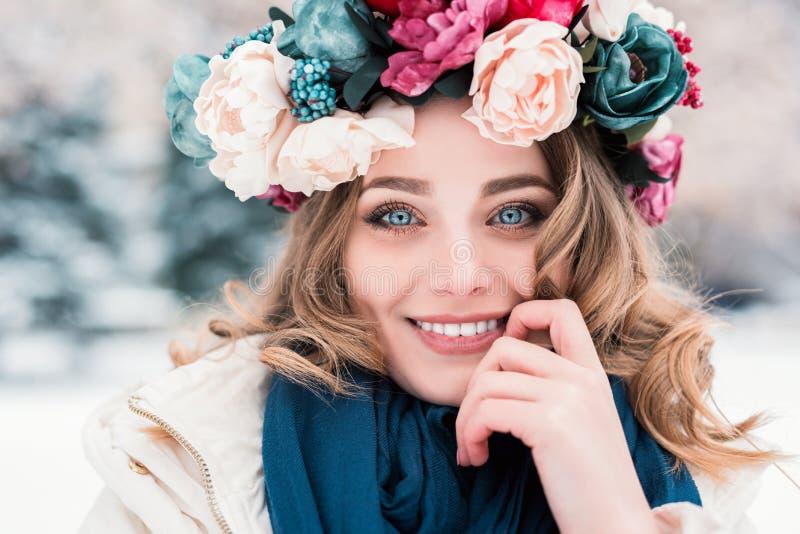 看在旁边佩带花卉头饰带冠状头饰冠和围巾被隔绝的冬天背景的年轻女人 图库摄影