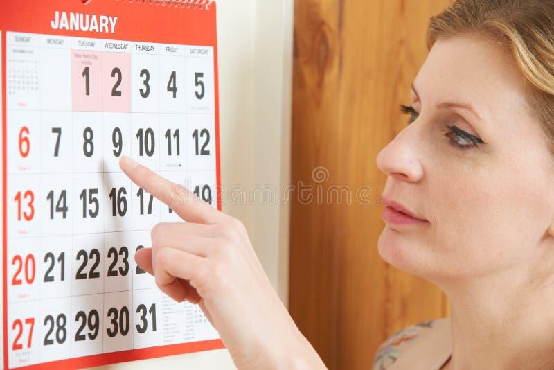 看在日历的担心的妇女日期 图库摄影