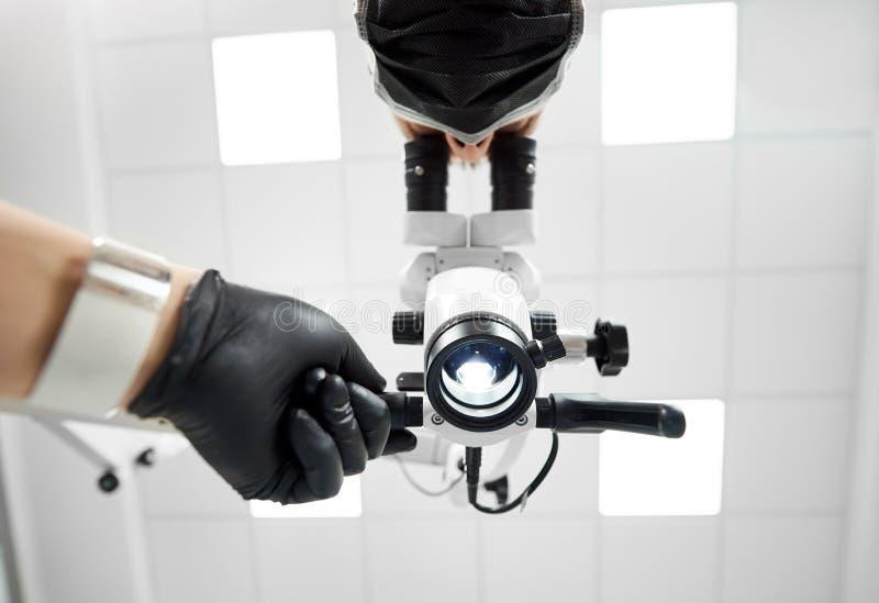 看在显微镜的一位男性牙医的Upwardview在专业牙科设备帮助下 免版税库存图片
