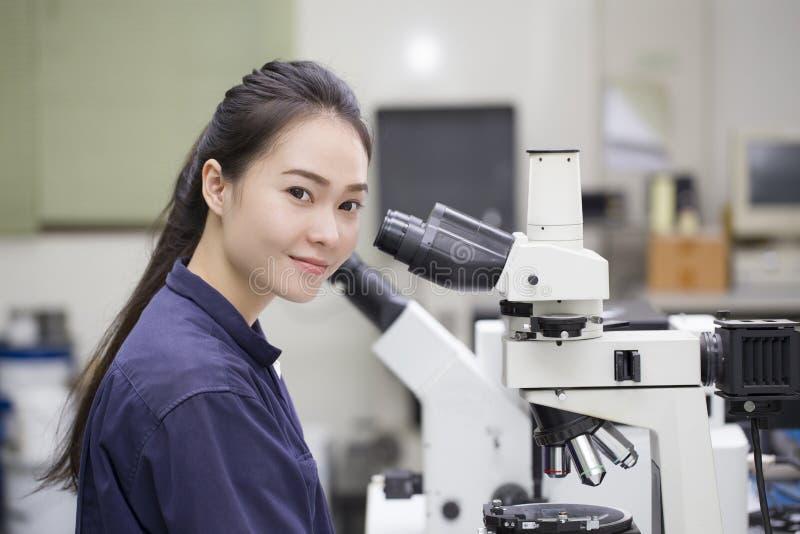 看在显微镜的女性科学家在实验室实验室 库存图片