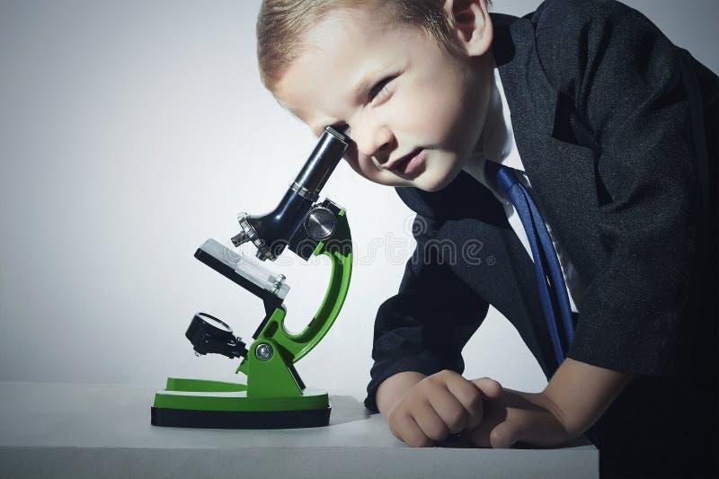 看在显微镜的衣服的男孩 聪明的子项 一点scientistGrey背景 免版税库存图片