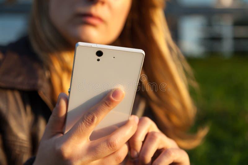 看在智能手机的妇女 免版税库存照片
