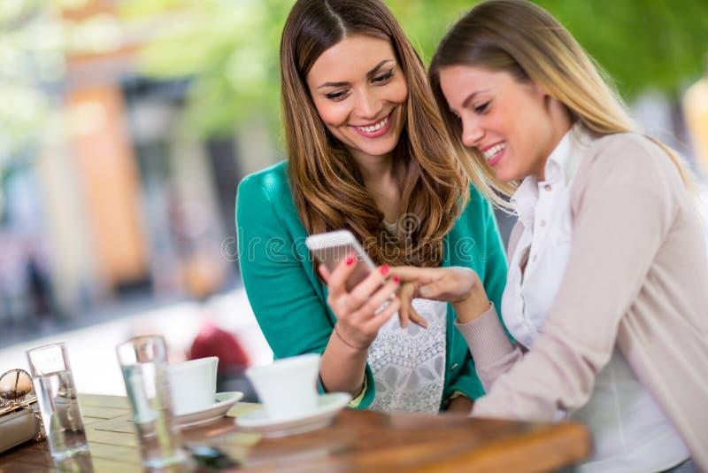 看在机动性的两个女孩图片在咖啡馆 免版税图库摄影