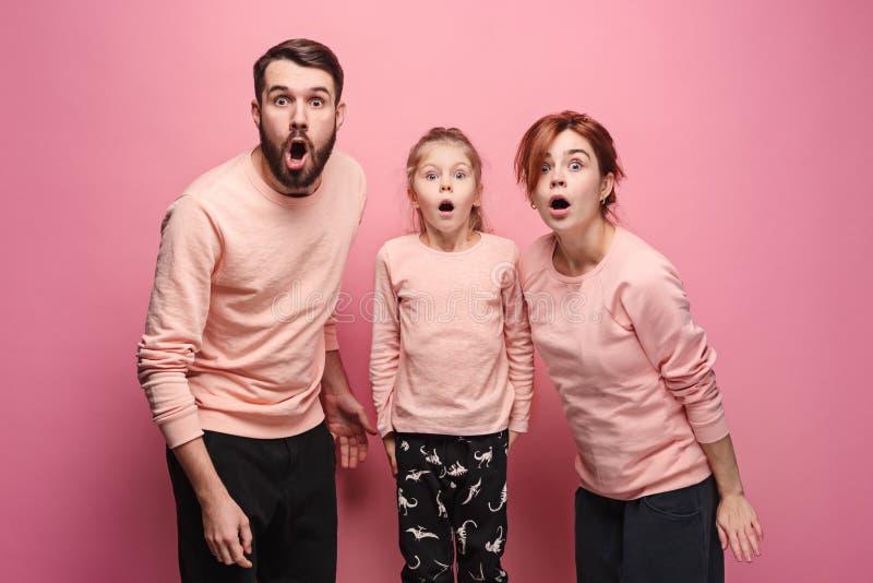 看在桃红色的惊奇的年轻家庭照相机 免版税库存照片