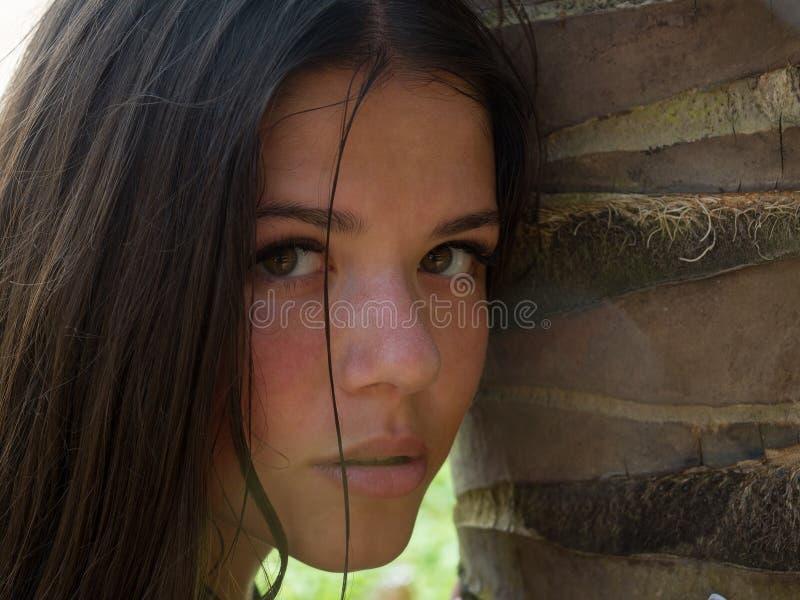 看在棕榈旁边的嫩妇女画象 免版税库存照片