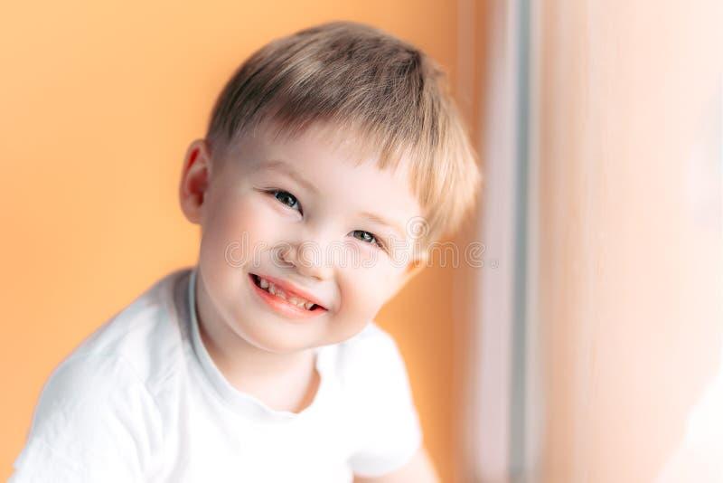 看在橙色背景的白肤金发的愉快的快乐的美丽的逗人喜爱的小男孩画象照相机 库存照片