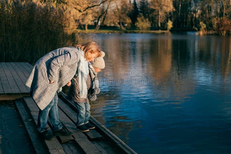 看在水的母亲和儿子在日落的秋天公园 图库摄影