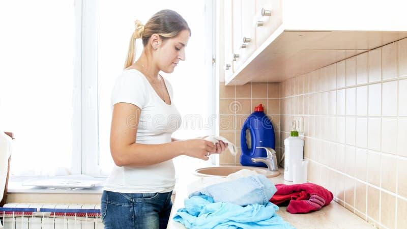 看在洗衣店的美丽的少妇肮脏的袜子 免版税图库摄影