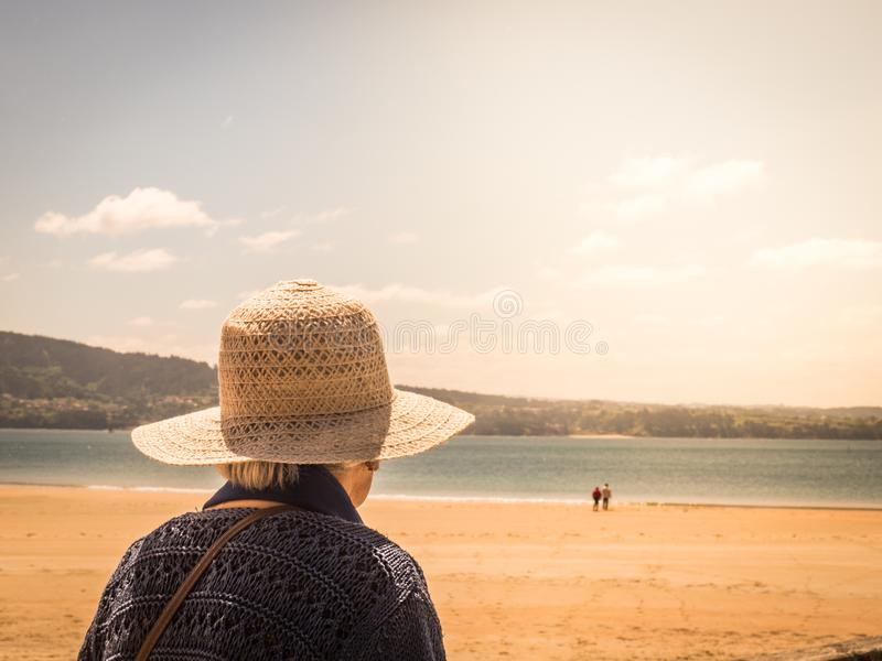 看在海滩的无法认出的老妇人一对夫妇 图库摄影