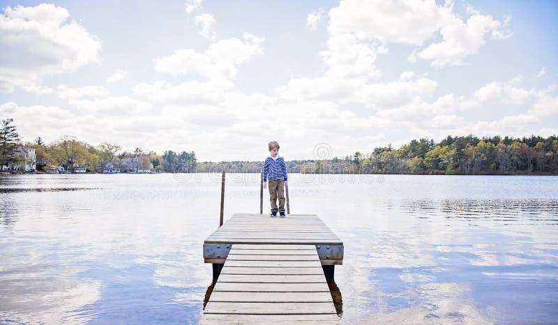 看在湖的船坞的男孩 免版税库存照片