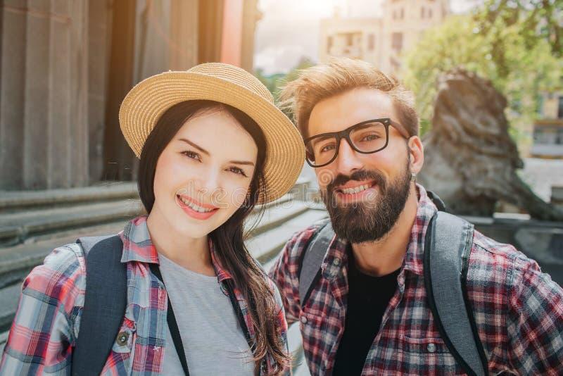 看在照相机和微笑的两个年轻游人的好的图片 男人和妇女接近台阶的立场外部 他们有 免版税图库摄影