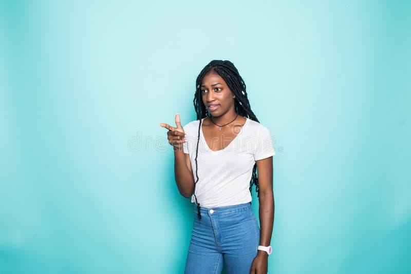 看在照相机和指向手指在拷贝空间的美满的美国妇女被隔绝在蓝色背景 库存照片