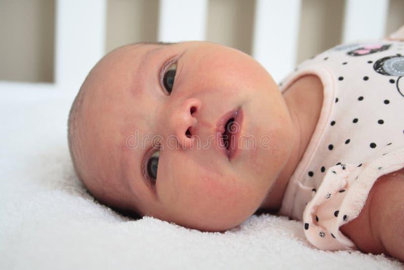 看在照相机的外套的新出生的女婴 免版税库存图片