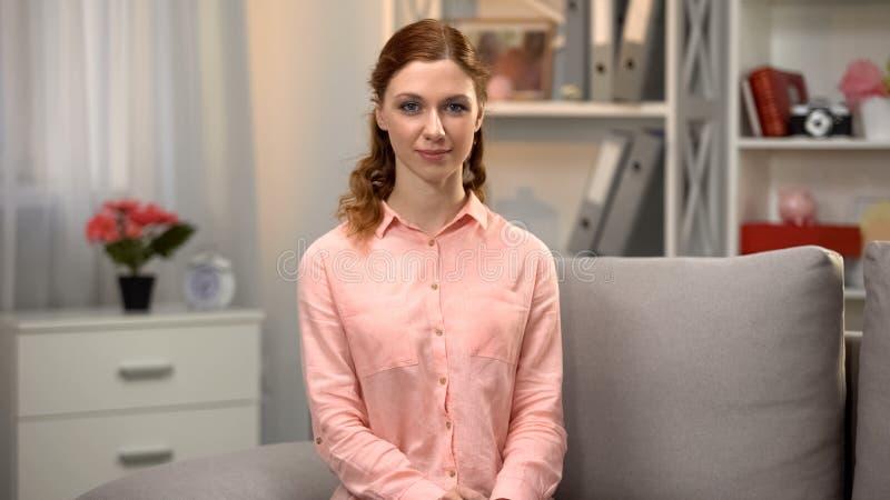 看在照相机的年轻白种人女性坐沙发,家庭舒适,休息 免版税库存图片