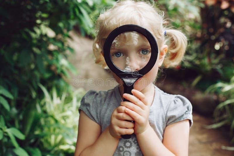 看在照相机的白种人女孩通过花通过放大镜 免版税图库摄影
