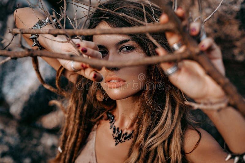 看在照相机的美丽的年轻女人接近的画象通过干燥分支 免版税库存图片