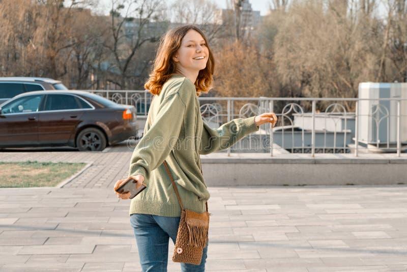 看在照相机的走的年轻微笑的女孩少年通过有棕色红色头发的后面在绿色毛线衣,晴朗的春日 免版税图库摄影