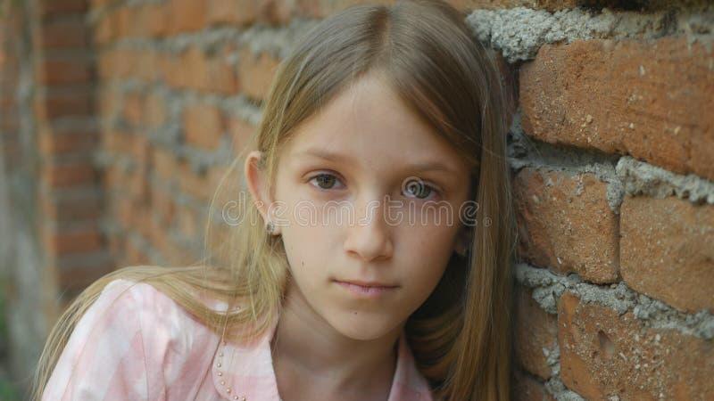 看在照相机,乏味女孩画象,不快乐的孩子面孔的哀伤的沮丧的孩子 免版税库存照片