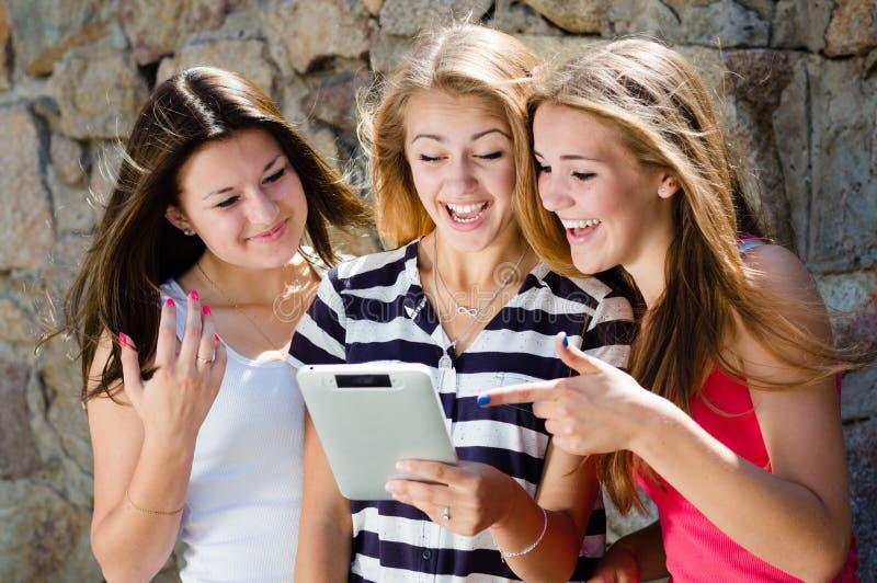 看在片剂个人计算机和笑在夏日的三个愉快的青少年的女朋友 免版税库存图片