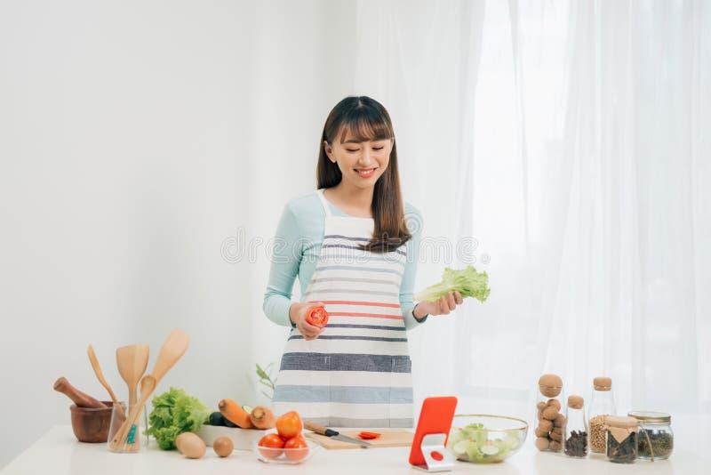 看在片剂的围裙的年轻愉快的妇女食谱在厨房里 E r r 库存照片