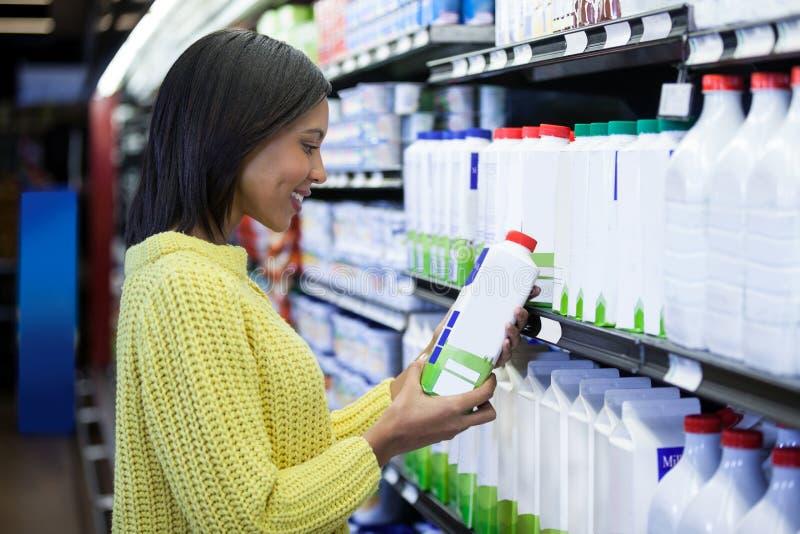 看在牛奶店部分的妇女牛奶瓶 图库摄影