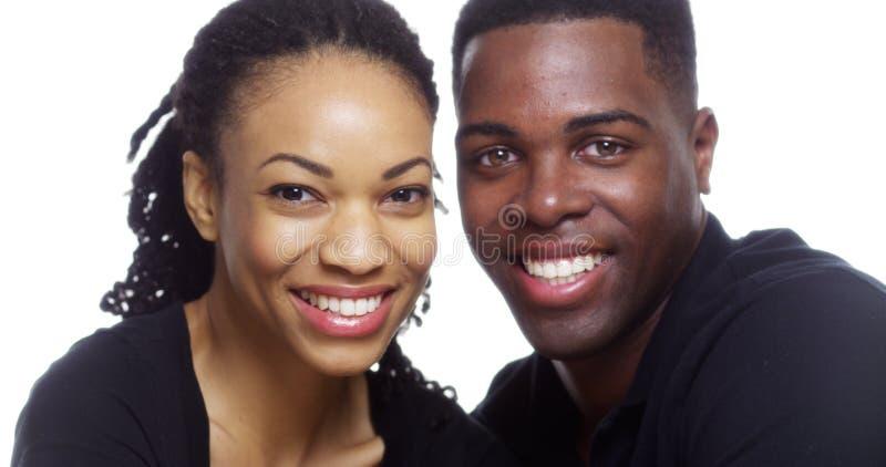看在白色背景的愉快的微笑的黑夫妇照相机 库存照片