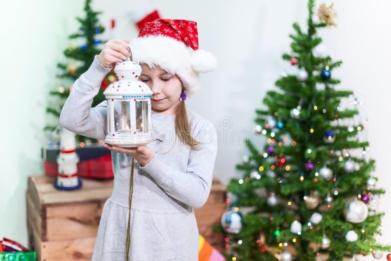 看在白色钢灯笼在她的手上,圣诞前夕里面的小女孩灼烧的蜡烛 库存图片