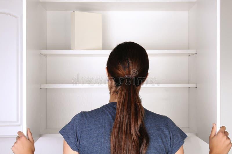 看在空的餐具室的妇女 免版税库存照片