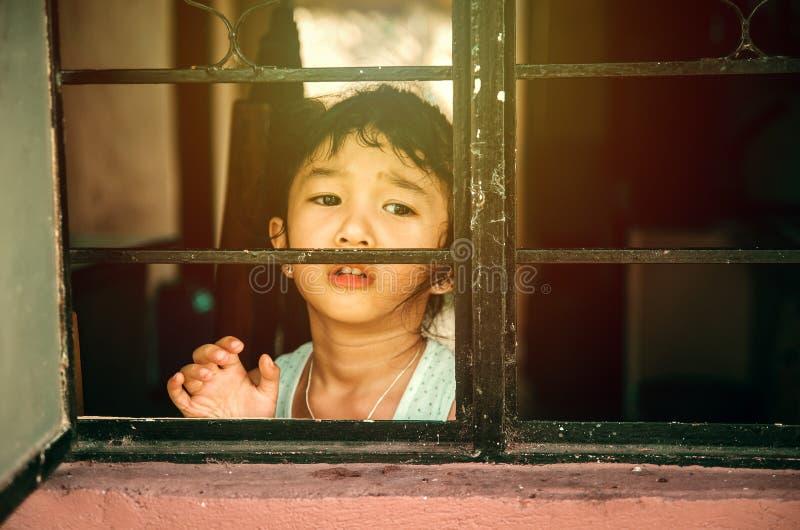 看在窗口外面的哀伤的女孩 免版税库存照片
