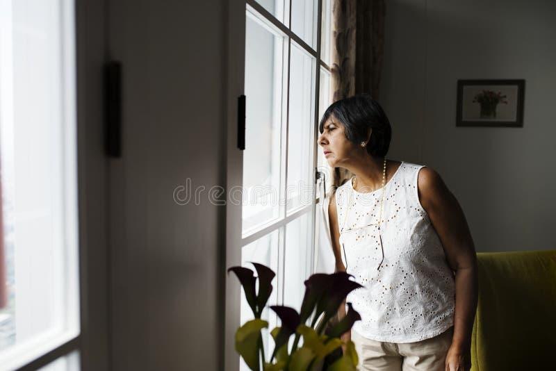 看在窗口外面的资深妇女 库存照片