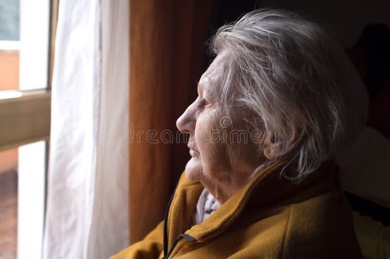 看在窗口的老妇人 免版税库存照片