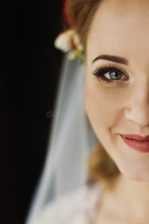 看在窗口,早晨婚礼preparati外面的美丽的新娘 免版税库存照片