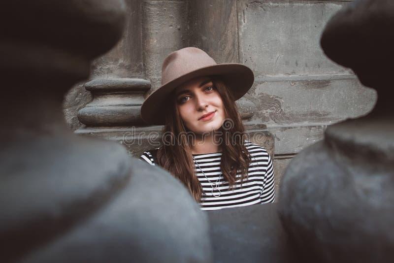 看在老房子的背景的帽子和镶边衬衣的画象美女照相机 r 库存照片