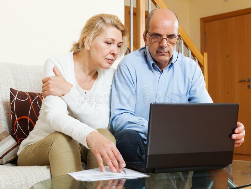 看在膝上型计算机的严肃的成熟夫妇文件 免版税库存照片