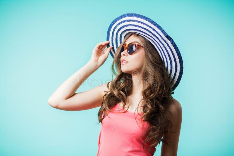 看在蓝色背景的帽子和太阳镜的美丽的少妇 秀丽,方式 免版税库存照片