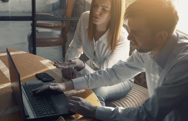 看在表上的年轻办公室夫妇的关闭膝上型计算机屏幕与严肃的表情一起 免版税库存照片